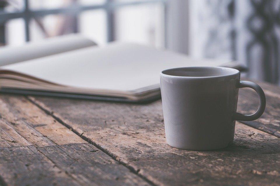 scrivania con tazza di caffè e agenda