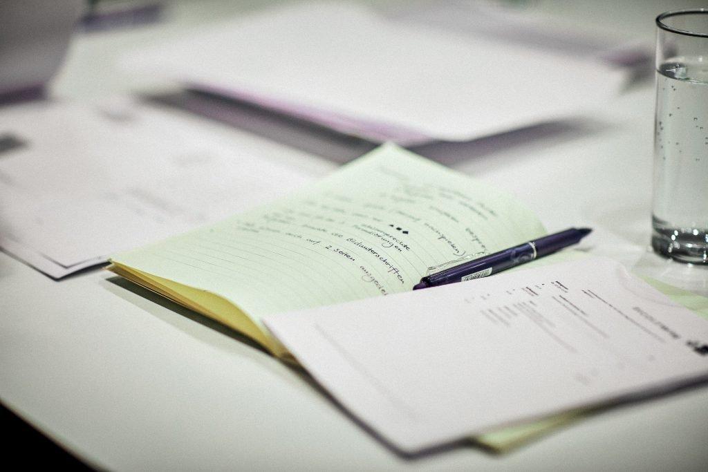 Stesura di un testo, quaderno e penna